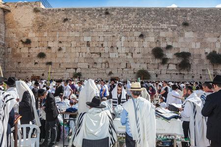 holies: JERUSALEM, ISRAEL - OCTOBER 12, 2014:  Hhuge crowd of faithful Jews wearing white prayer shawls and black long-skirted coats. Morning autumn Sukkot