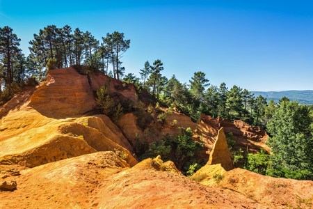 yellow ochre: Roussillon, Red village of Provence. Multi-colored outcrops - from yellow to red-orange. Green trees create beautiful contrast from ochre Stock Photo