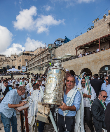believing: JERUSALEM, ISRAEL - OCTOBER 12, 2014: Morning autumn Sukkot. The area in front of Western Wall of  Temple. Crowd of Jewish worshipers in white wearing prayer shawls. Sefer Torah in a magnificent case keeps believing Jew
