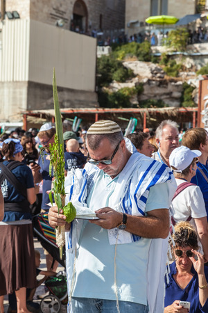 holies: JERUSALEM, ISRAEL - OCTOBER 12, 2014: The area in front of the Western Wall of the Temple filled with people. Morning autumn Sukkot. Many brought prayer books and four ritual plants