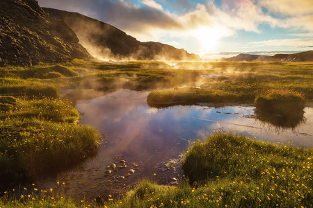 lake: Sunrise Park Landmannalaugar. White nights in Iceland. Above the source of thermal water steam rises