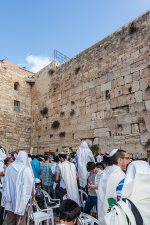 sukkoth: JERUSALEM, ISRAEL - OCTOBER 12, 2014: The area in front of Western Wall of  Temple filled with people. Crowd of faithful Jews wearing prayer shawls. Morning autumn Sukkot
