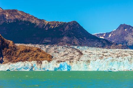 descends: Massive glacier descends into the emerald water.
