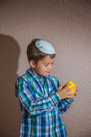 sukkoth: Beautiful seven year old boy in white jewish knitted skullcap is holding etrog.  Etrog  - a ritual fruit for the holiday of Sukkot