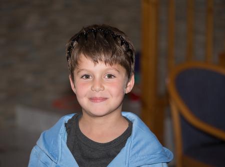 ojos verdes: Muchacho adorable con los ojos verdes en una corona de juguete