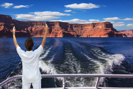 admiring: Middle-aged woman in white at the stern of the ship admiring the beauty of nature. Artificial lake Powell on the Colorado River, USA. The lake is surrounded by picturesque beaches of the orange sandstone