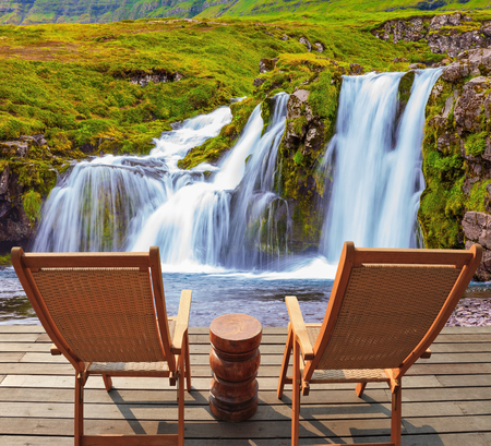deck chairs: Deck chairs on a wooden platform waiting for tourists.  Threaded full-flowing waterfall Kirkyufell Foss on the grassy mountains Stock Photo