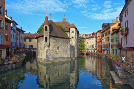 ancient prison: The charming ancient city of  Annecy in Provence. Clear early morning. The bastion turned into prison, is reflected in channel water