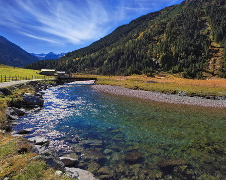 spanned: Austrian Alps.  Starting famous Krimml waterfalls. Crystal clear water sparkles in the midday sun. Through the narrow creek wooden bridge spanned