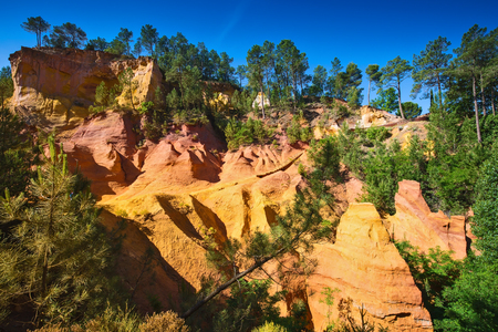 roussillon: Unique red and orange hills in the province of Languedoc - Roussillon, France. Green trees create a beautiful contrast with the bright ocher Stock Photo