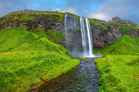 waterfall with sky: The warm July day in Iceland. Seljalandsfoss waterfall. Rainbow decorates drop of water Stock Photo