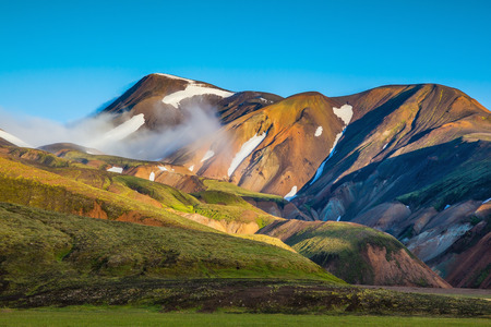 hollows: Early summer morning in the National Park Landmannalaugar, Iceland. In the hollows of rhyolitic mountain snow