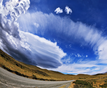 improbable: Gray dirt road in the Chilean national park to Torres del Paine. Improbable form the clouds created by glaciers, shine under the sun. On the horizon mountains with snow tops are visible. The photo is made a lens the Fish eye
