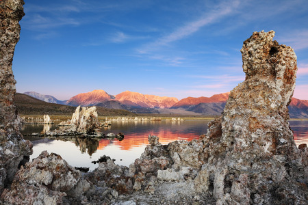calcareous: Outliers - bizarre limestone calcareous tufa formation on the smooth water of the lake. The magic of Mono Lake. Orange sunset