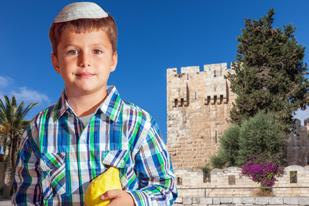 etrog: Sukkot in Jerusalem. Charming seven year old boy in white festive skullcap with etrog