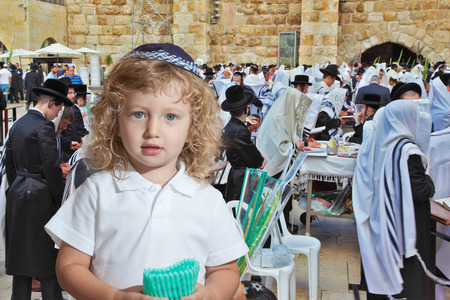 western wall: Adorable little boy with long blond curls and blue eyes in knitted skullcap. He stands at the main Jewish shrine - Western Wall of Temple. The Jewish holiday of Sukkot