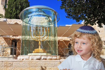 skullcap: Cute little boy with long blond curls and blue eyes in a knitted skullcap. He stands at the Golden Menorah in Jerusalem. The Jewish holiday of Sukkot
