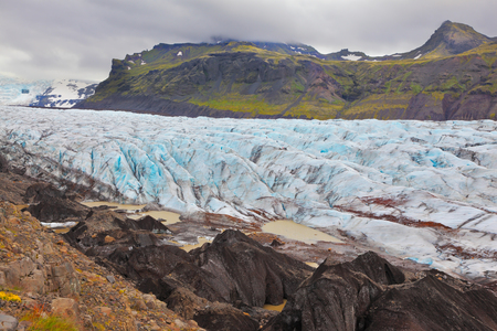 unexplored: Skaftafell National Park. The part of the huge Vatnajokull glacier. Blue ice covered ground black volcanic ash