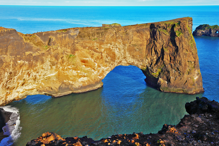 colossal: Cape Dyrholaey in southern Iceland. Sunset in July. The colossal rock in the sea in the form of an elephant