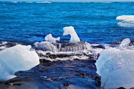 ices: The Arctic Ocean. Iceland. Floating  ices  Yokulsarlon  lagoon on the beach with black sand