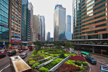 flower beds: HONG KONG - DECEMBER 11, 2014: Hong Kong Special Administrative Region. Fancy driving roundabout with colorful flower beds. Modern skyscrapers and narrow streets between them