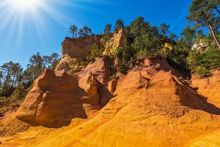 roussillon: Unique red and orange hills in the province of Roussillon, France. Coniferous forests create a beautiful contrast with the color of ocher