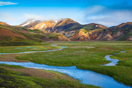 hollows: Snow lies in the hollows of colorful rhyolite mountains. Green Valley is flooded with melt water.  Early summer morning in the National Park Landmannalaugar, Iceland