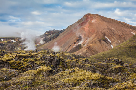 hollows: Picturesque rhyolite mountains surround the valley. In the hollows of the mountains from the ground rises  steam.  Summer morning in the National Park Landmannalaugar, Iceland