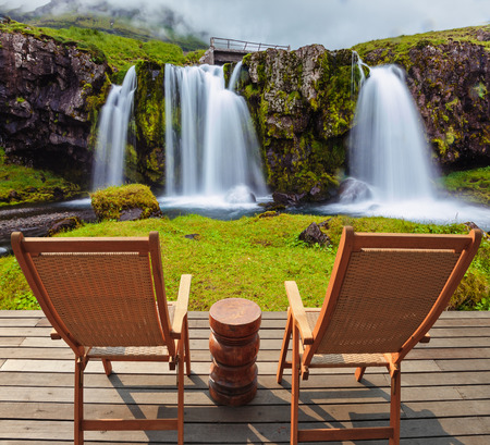 deck chairs: Deck chairs on wooden platform waiting for tourists.  Threaded full-flowing waterfall Kirkyufell Foss on the grassy mountains