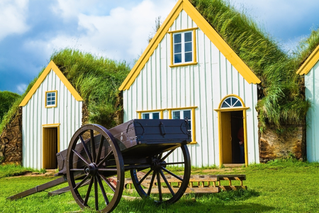 reconstituted: The ancient two-wheeled wooden cart on the front lawn. The village first settlers in Iceland. The reconstituted village - Pioneer Museum - Viking