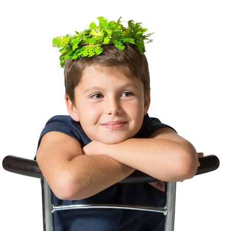 seven year old: Very beautiful seven year old boy in a carnival wearing a crown of shiny green leaves. He sits astride a chair