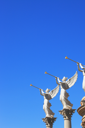 fanfare: The statues of winged troubadours against the blue sky decorated capitals of the columns. Stock Photo