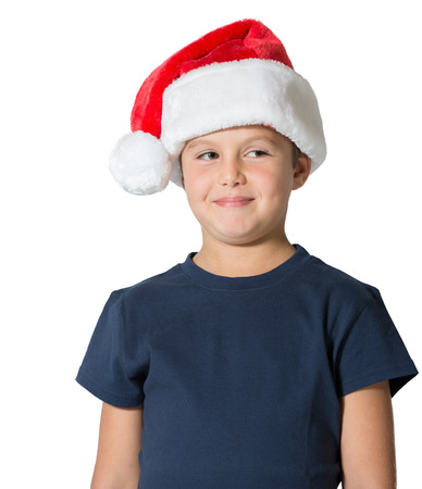 cheerfully: Charming seven-year boy in Santa Claus hat cheerfully smiles. Photo executed on a white background