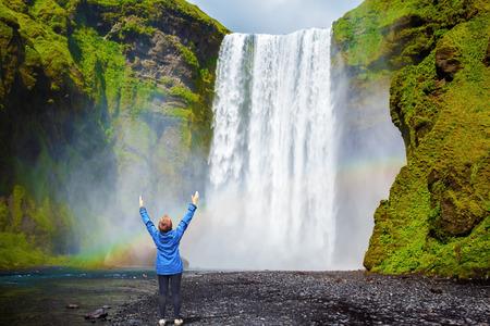 Ciekawe wodospad w Islandii - Skogafoss. Malownicze ogromna tęcza pojawia się mgły wodnej. Kobieta w średnim wieku - turystyczny wstrząśnięty piękno wodospadu