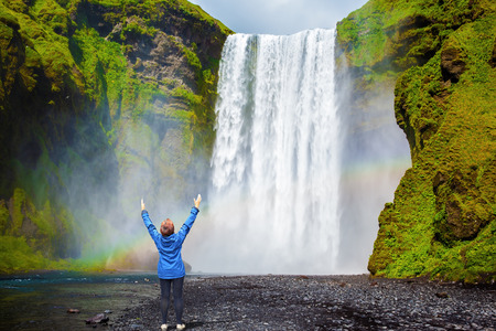 Interesting waterfall in Iceland - Skogafoss. Picturesque huge rainbow appears in the water mist. Middle-aged woman - tourist shocked beauty waterfall Standard-Bild