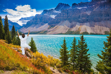 azure: The elderly woman in white clothes for yoga carries out an asana  Tree on  bank of the lake. The azure waters of lake surrounded by Rocky Mountains and lush autumn yellow and orange vegetation