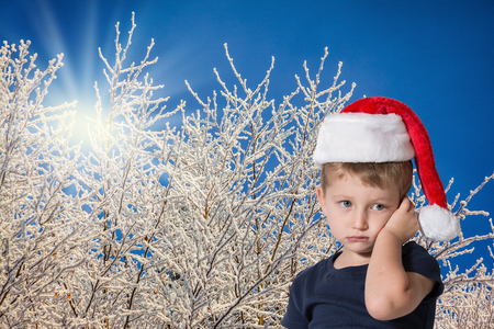snow day:  The child has sad blue eyes and fair soft hair. The charming little boy in red cap of Santa Claus. Photo executed on background of snow-covered forest