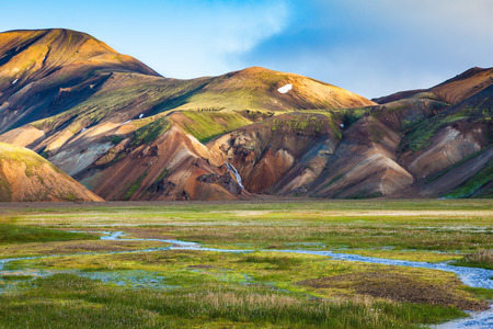 hollows: Green Valley is flooded with melt water. Snow lies in the hollows of colorful rhyolite mountains. Early summer morning in the National Park Landmannalaugar, Iceland
