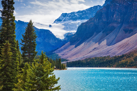 "Autumn sunny day to the Rocky Mountains of Canada on Lake Bow. The lake is surrounded with rocks and fir-trees. Glacier ""Crowfoot"" glows in bright sunlight"