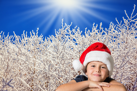 seven year old: Beautiful seven year old boy in red hat of Santa-Claus smiling  on the background of the winter forest
