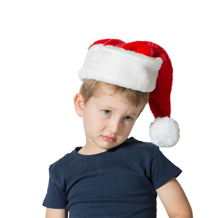 three year old: Adorable three year old boy in red cap of Santa Claus. The child has sad blue eyes and blond soft hair. Photo executed on a white background Stock Photo