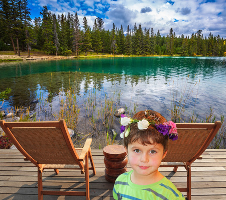 lounges: The beautiful boy in carnival wreath. Two convenient chaise lounges on the bank of round lake