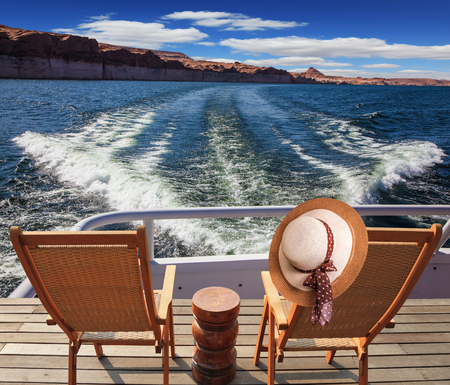 cut through: At the stern of the vessel are two deck chairs. On the back of one hanging elegant ladies straw hat. Waves from the boat cut through the Lake Powell on the Colorado River