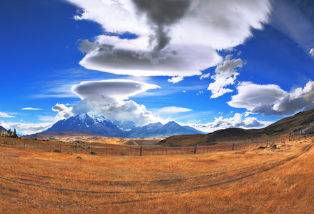 glisten: The Chile National Park Torres del Paine. Incredible shaped clouds formed by glaciers glisten in the sun. On the horizon are seen mountains with snow-capped peaks. Picture taken with a fisheye lens