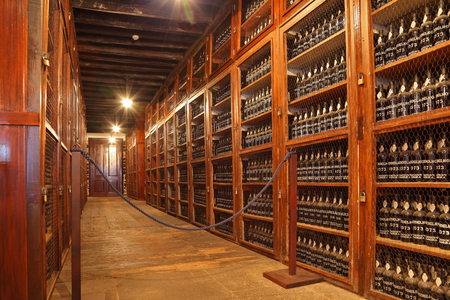 repository: FUNCHAL, MADEIRA - OCTOBER 08, 2011: Long rows of shelves made of mahogany. The shelves are made with sweet wine bottles Madera.  Museum - repository of expensive vintage wine Madera.