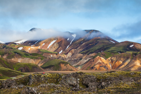 hollows: Snow lies in the hollows of multicolored rhyolite mountains. Early summer morning in the National Park Landmannalaugar, Iceland
