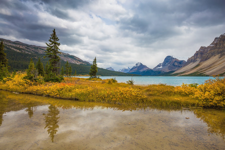 reflects: Banff National Park. The smooth water reflects the cloudy sky. Snow-capped mountains and glaciers surroundings Bow Lake