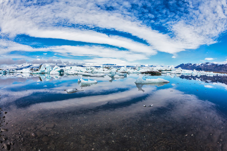blue lagoon: Ice lagoon in Iceland. Magnificent summer morning in the ocean gulf with floating ice floes. The layered clouds fanning are reflected in a smooth surface of water Stock Photo