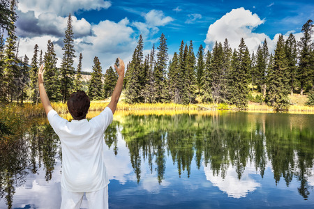 salutation: Jasper National Park in the Rocky Mountains of Canada. Patricia Lake. Middle-aged woman, dressed for yoga, Sun Salutation on the shore of small lake