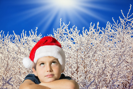 seven year old: Very beautiful seven year old boy in red hat of Santa-Claus smiling  on the background of the winter forest Stock Photo